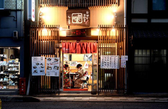 Dos turistas, vestidas con atuendo tradicional, esperan la comida en un restaurante. Alquilar kimono en invierno ...