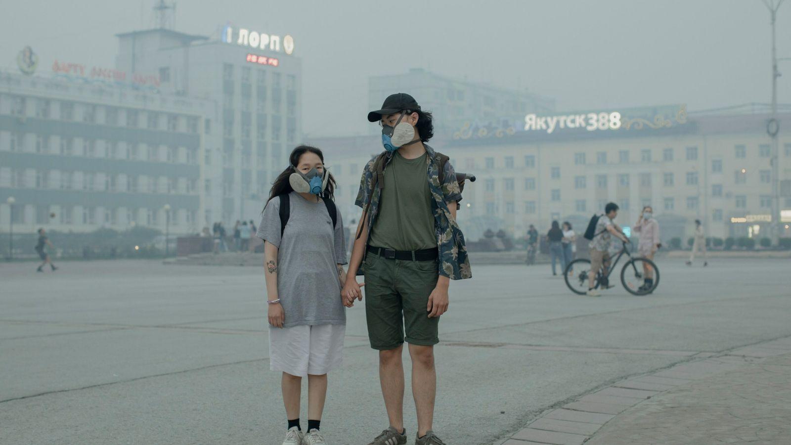 27 de julio - Elizabeth Yefimova, de 18 años, y Ilya Alekseyev, de 20, llevan máscaras respiratorias mientras el ...