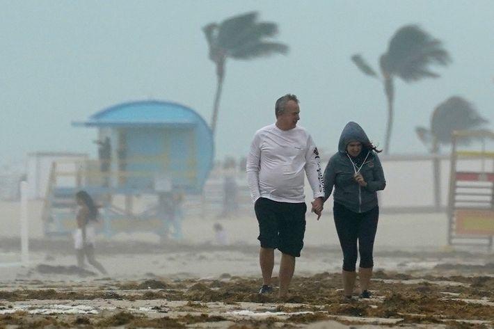 Una pareja camina por la playa mientras la tormenta tropical Eta golpea a Miami Beach, Florida, ...