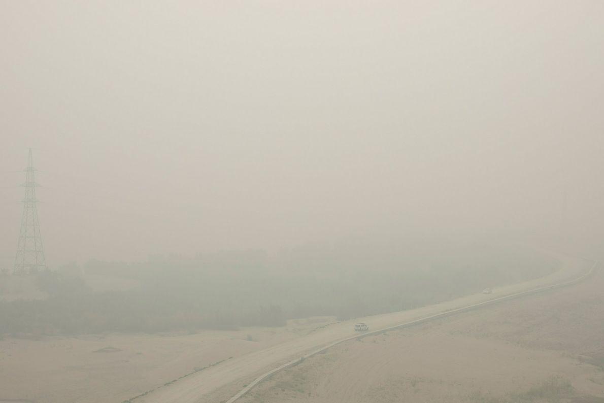 1 de agosto - Los coches se arrastran a través del humo espeso que se cierne sobre ...