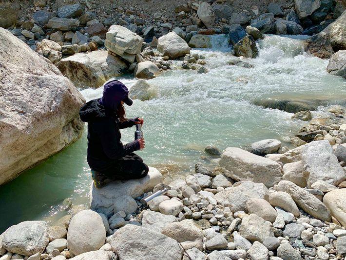 Heather Clifford, científica especialista en clima de la Universidad de Maine, recoge agua de un arroyo ...