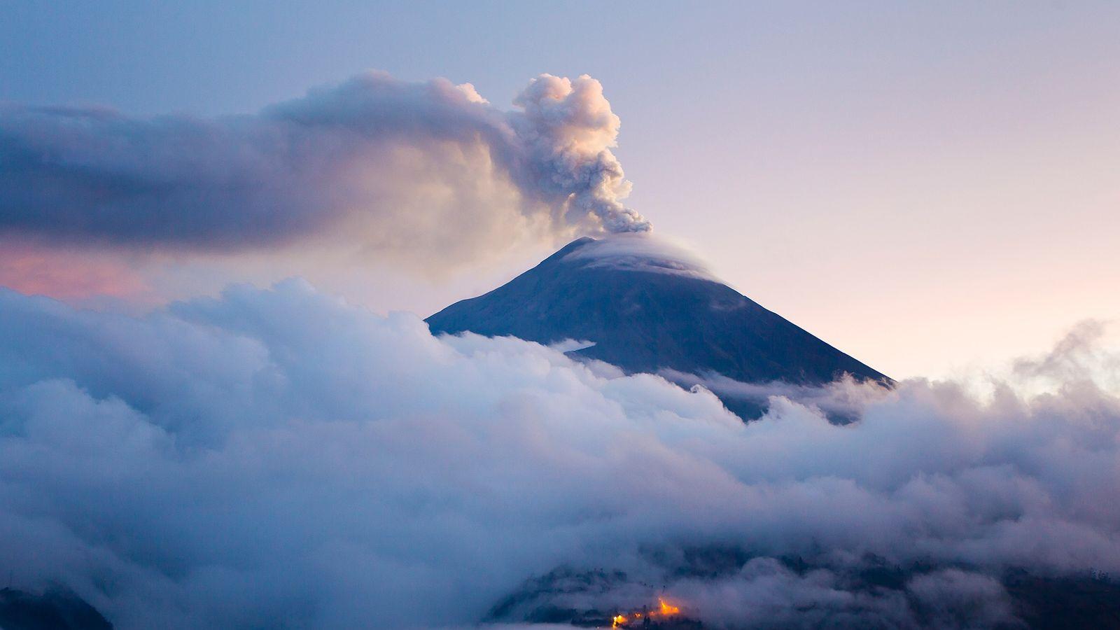 El volcán Tungurahua en erupción en el crepúsculo. Una de las formas en que la Tierra ...