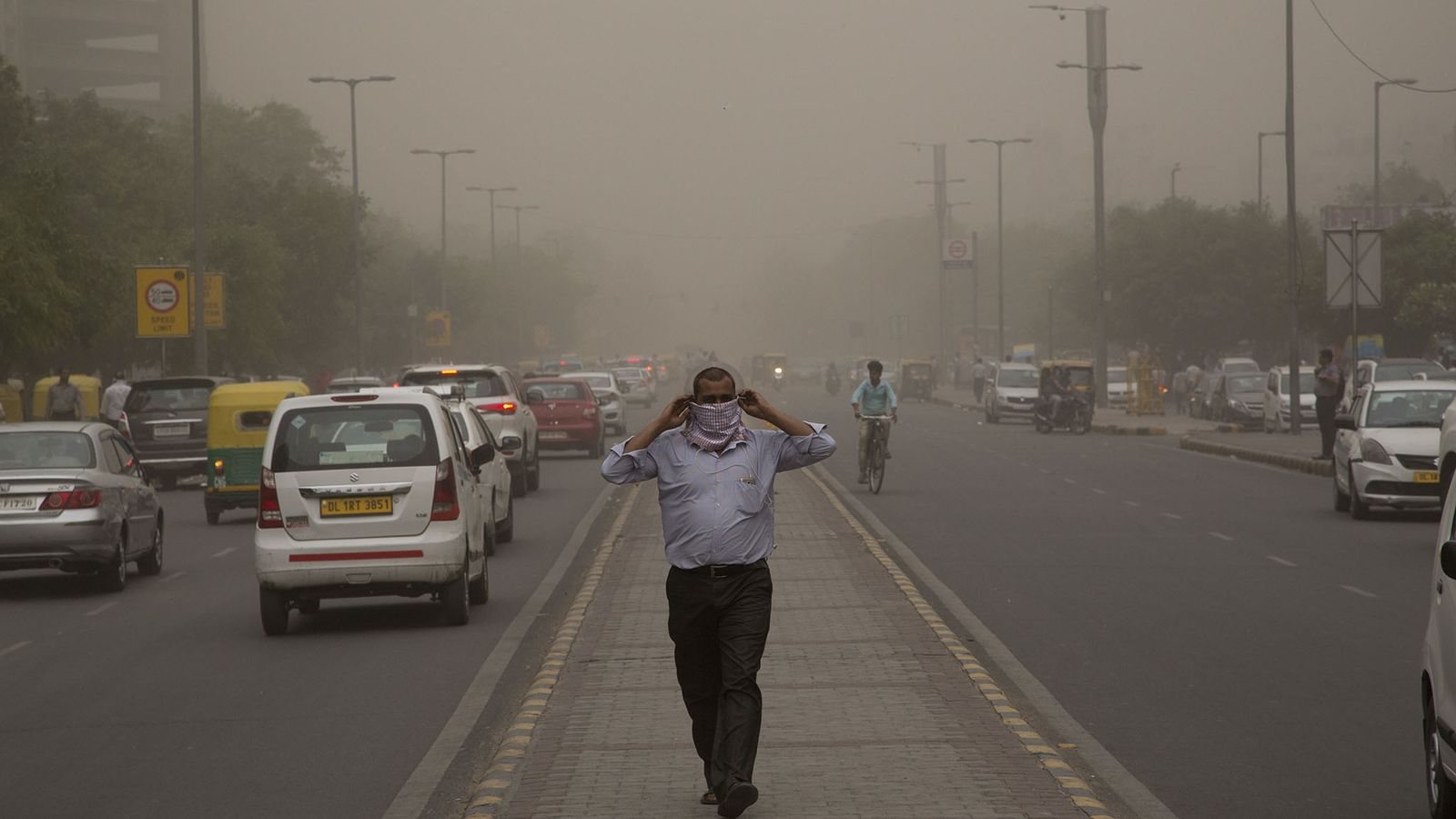 Un hombre se cubre la nariz con un pañuelo mientras la tormenta de polvo envuelve la ...