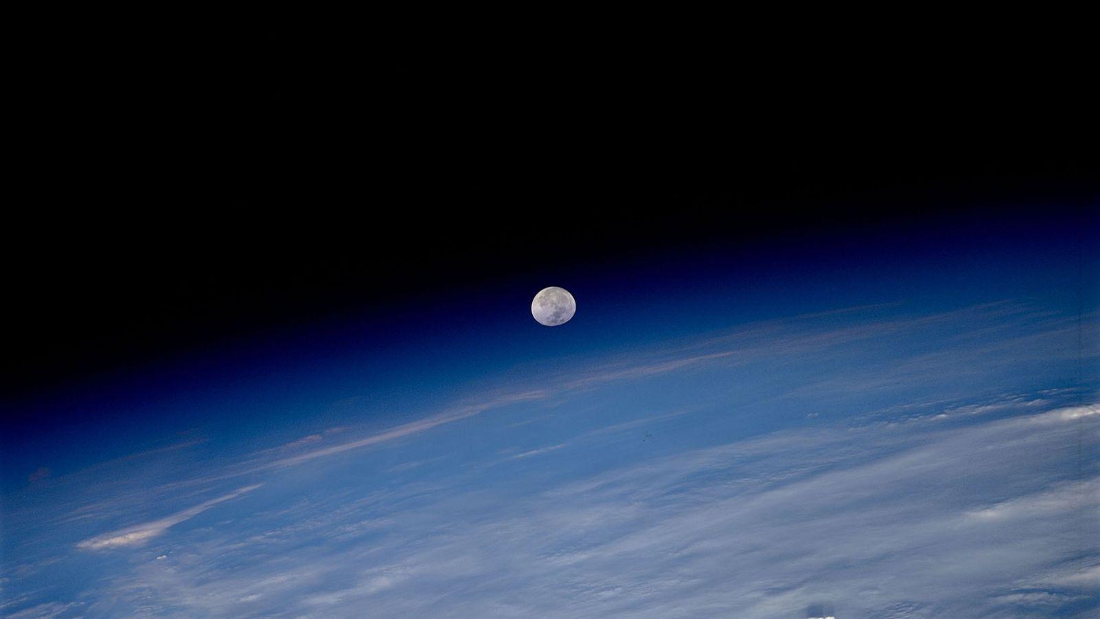 En esta fotografía tomada desde la Estación Espacial Internacional, la luna parece estar suspendida entre la ...