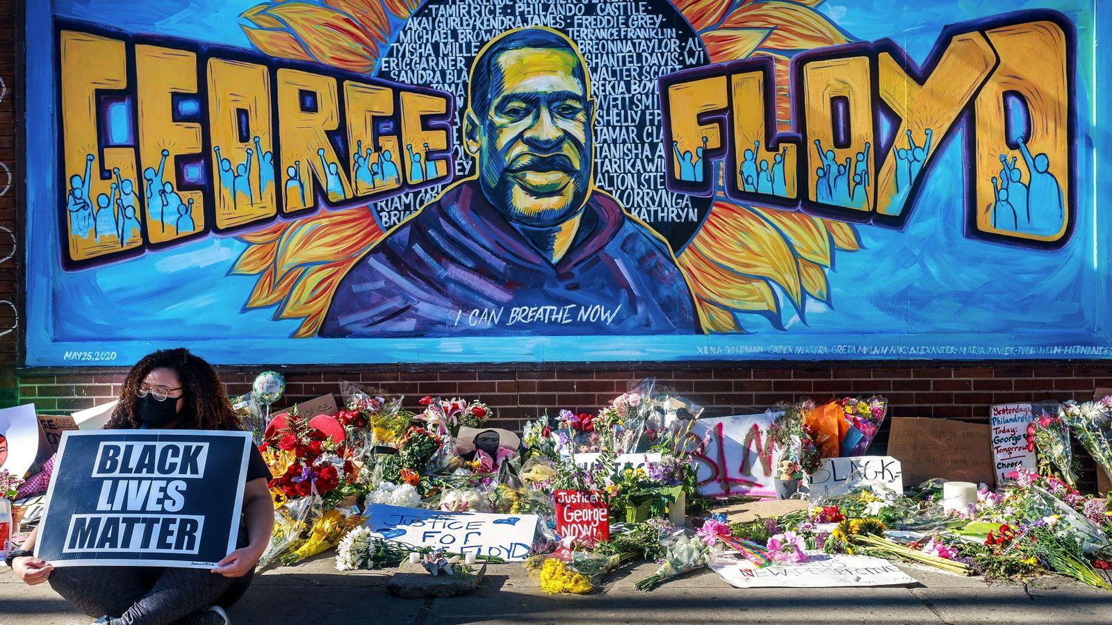 Flores, letreros y globos son dejadoscerca de un monumento improvisado a George Floyd, cerca del lugar ...