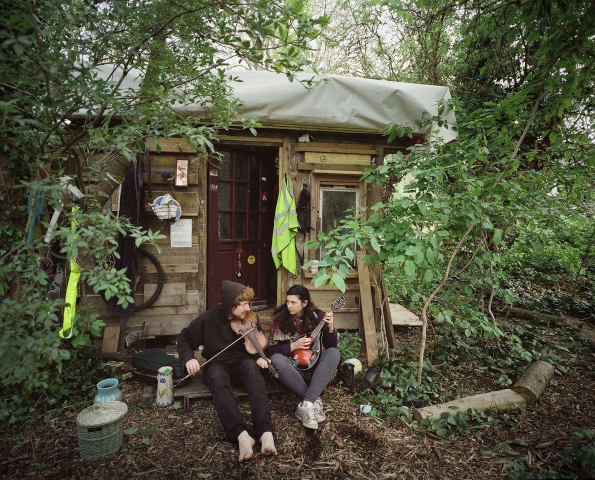 Una pareja está sentada frente a su casa en el área arbolada de Grow Heathrow. Él ...