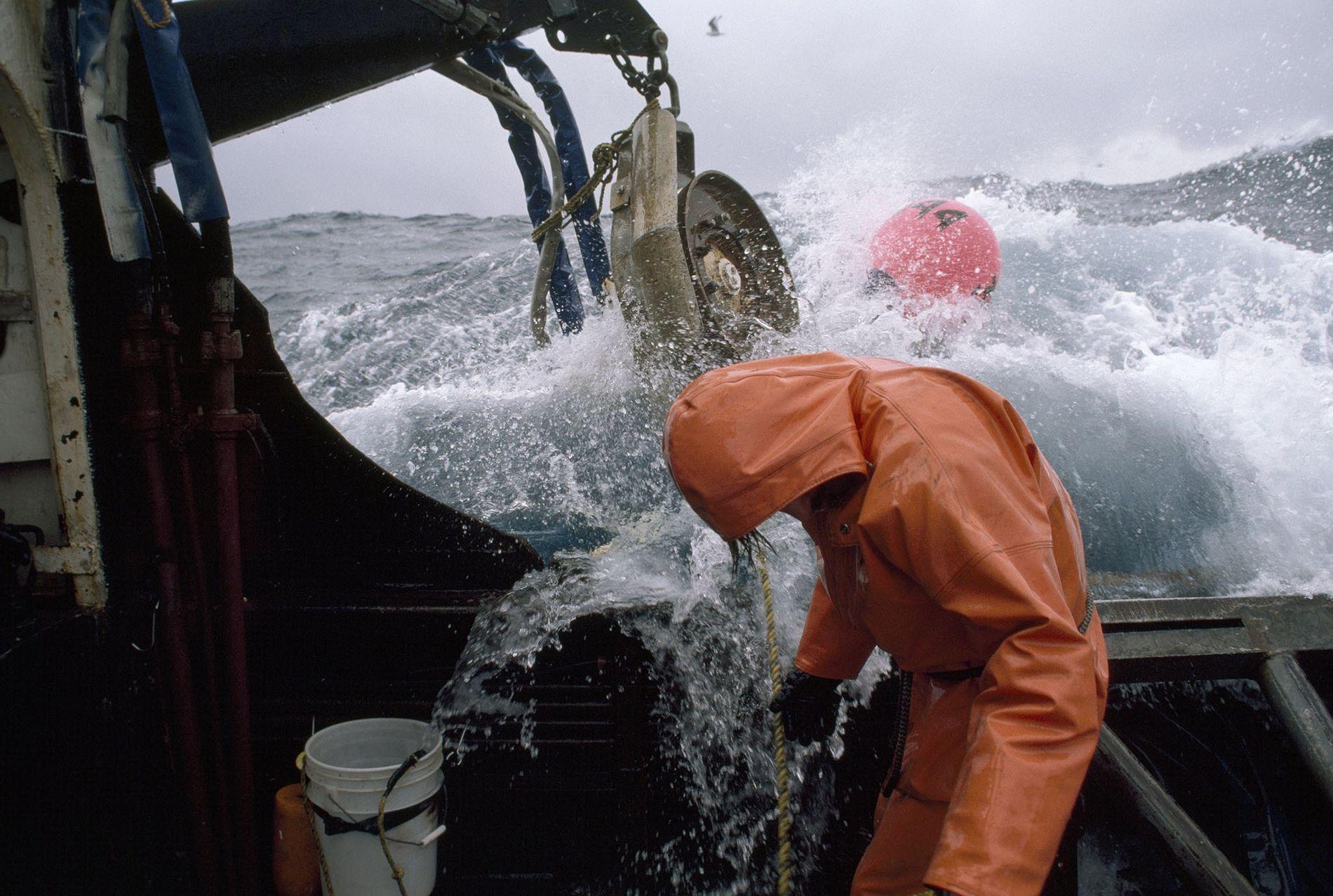 Un pescador revisa sus líneas de pesca mientras se encuentra pescando en alta mar. Alta mar ...