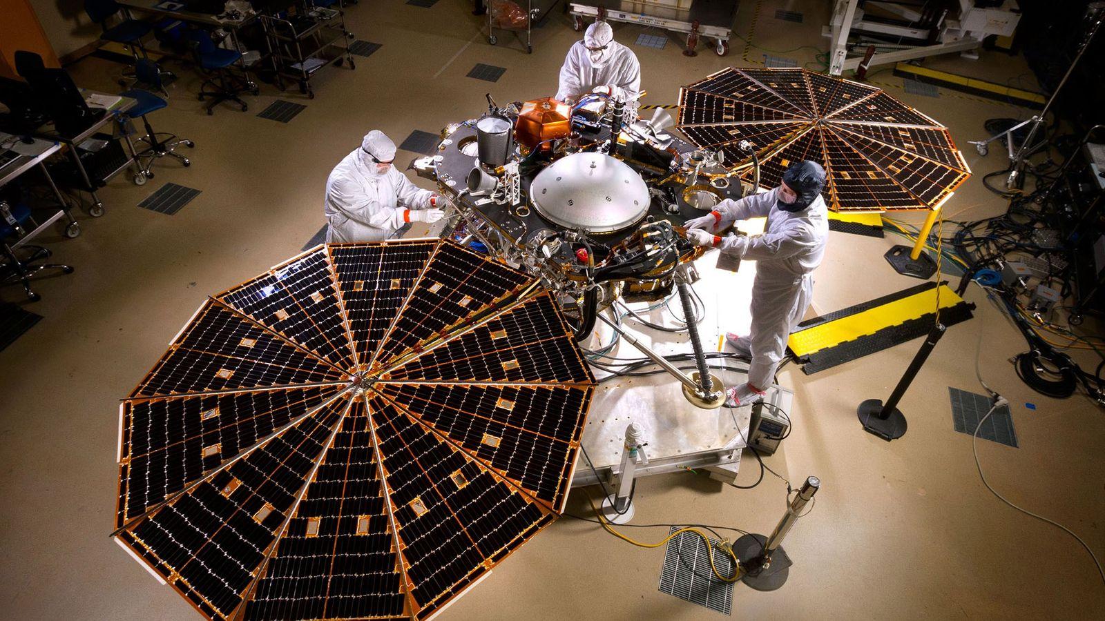 Los ingenieros despliegan los paneles solares del aterrizador InSight de la NASA dentro de una habitación ...