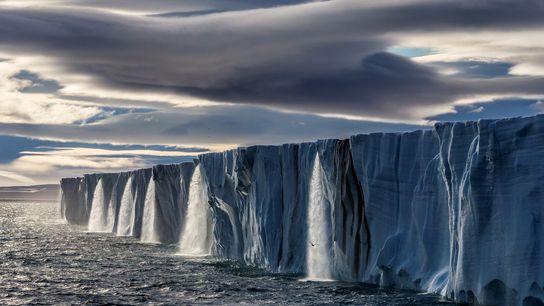 El agua de deshielo cae a borbotones desde una capa de hielo en la isla de ...