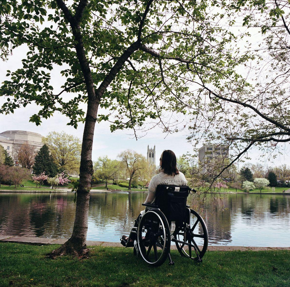 Katie se sienta detrás de un árbol en Wade Lagoon en Cleveland, Ohio. En una caminata ...