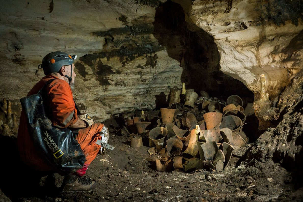 El explorador de National Geographic Guillermo de Anda examina un depósito de vasijas rituales dentro de ...