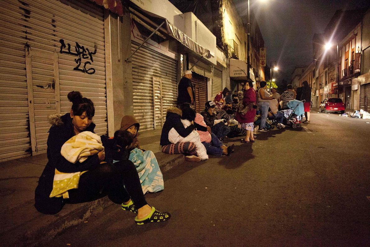Las personas se reúnen en una calle en el centro de la Ciudad de México durante ...