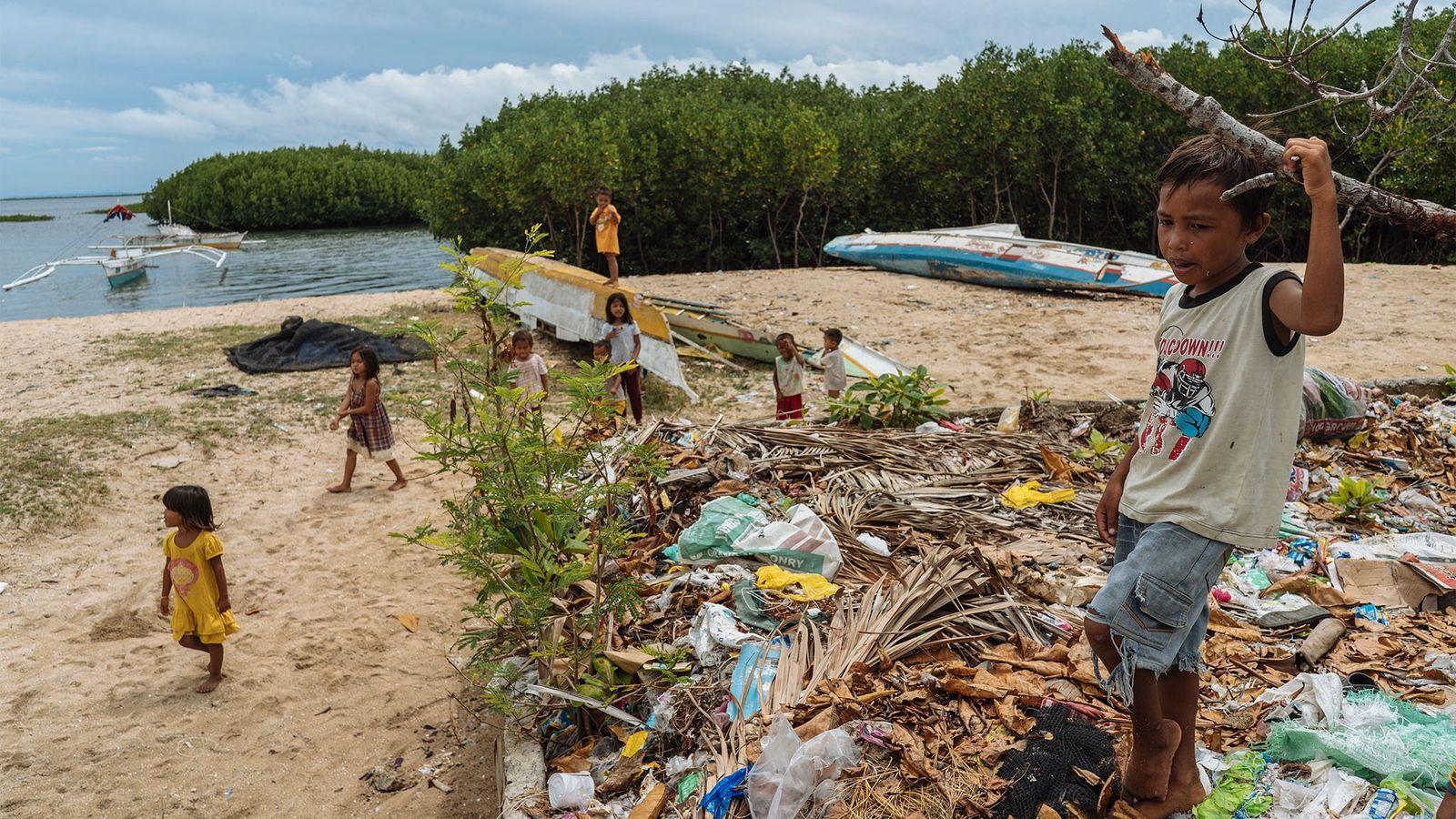 Unos niños juegan junto a un vertedero en Bohol, Filipinas. Con la marea alta y las ...