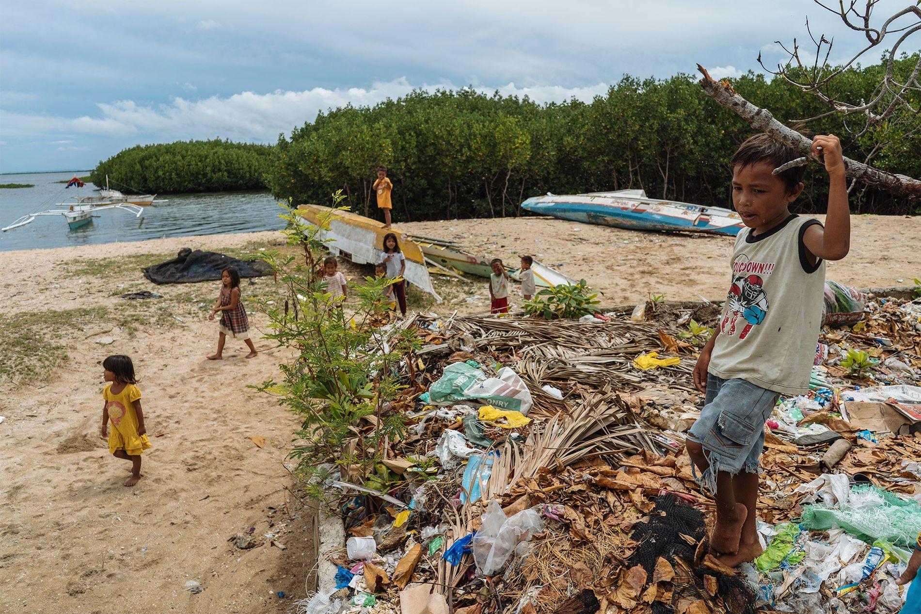 Unos niños juegan junto a un vertedero en Bohol, Filipinas. Con la marea alta y las lluvias, los residuos del vertedero llegan al agua. Las Filipinas son el centro de la biodiversidad marina del mundo, pero se encuentra en el tercer puesto después de China e Indonesia en contaminante de los océanos.