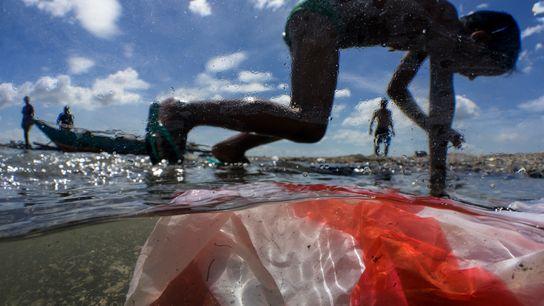 Niños juegan en la playa de Manila Bay, contaminada con residuos domésticos, plásticos y otro tipo ...