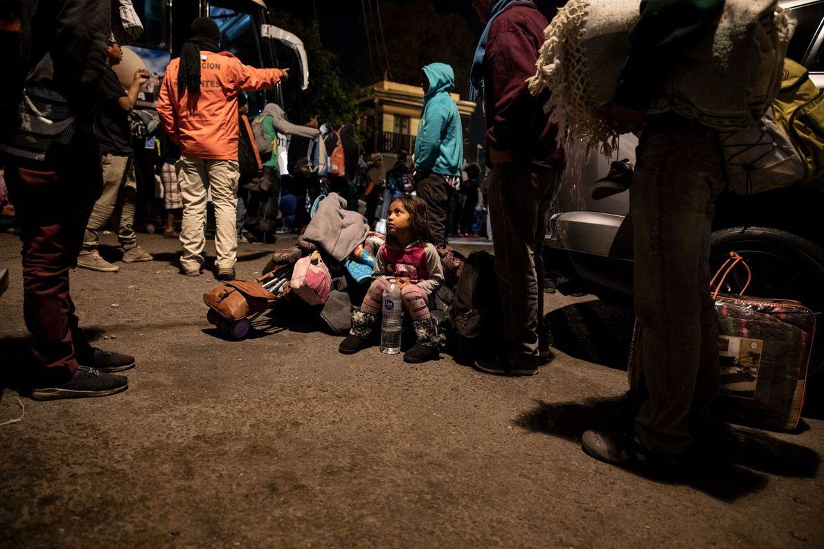 Una niña espera a que su madre y su tía recojan sus pertenencias del autobús. Los ...