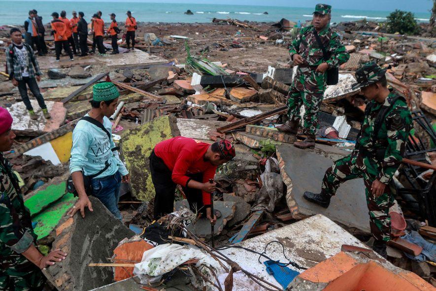 Las personas buscan entre los escombros, luego del tsunami mortal en la provincia de Lampung, Indonesia, ...