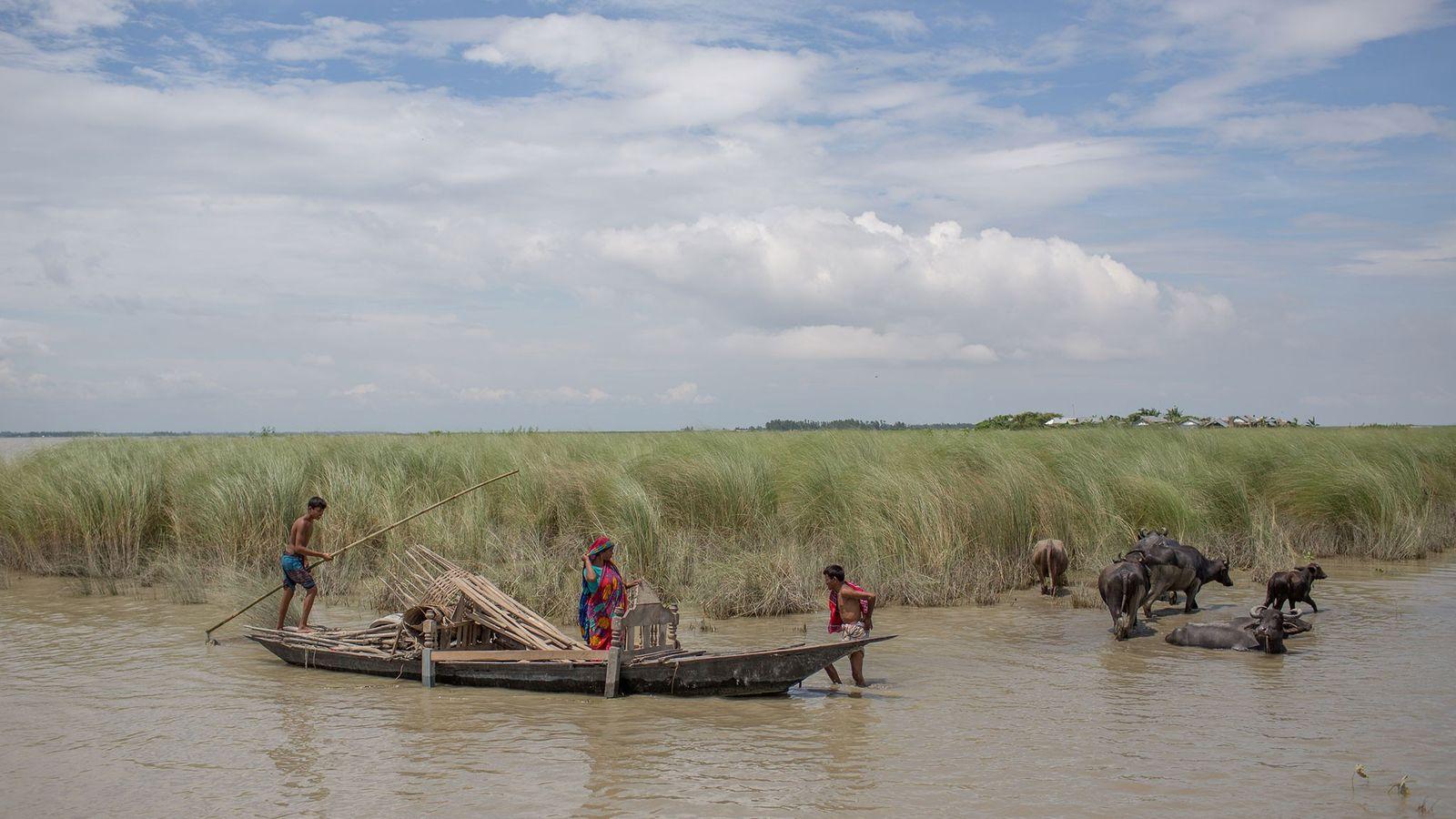 La gente lleva sus bienes importantes en barco en una aldea afectada por inundaciones en Gaibandha, ...