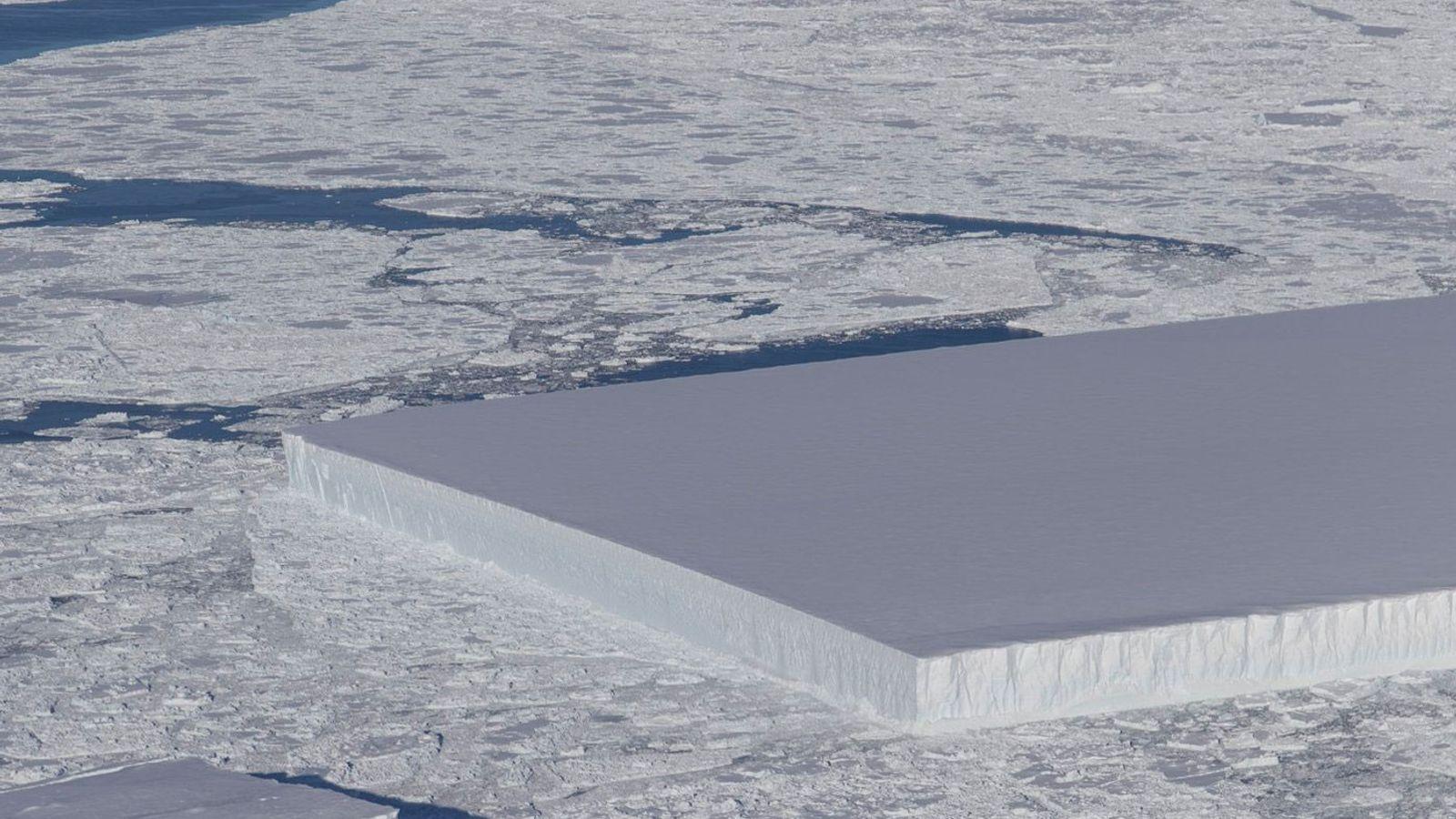 Desde un vuelo del IceBridge puede observarse a la derecha un iceberg tabular que flota entre ...