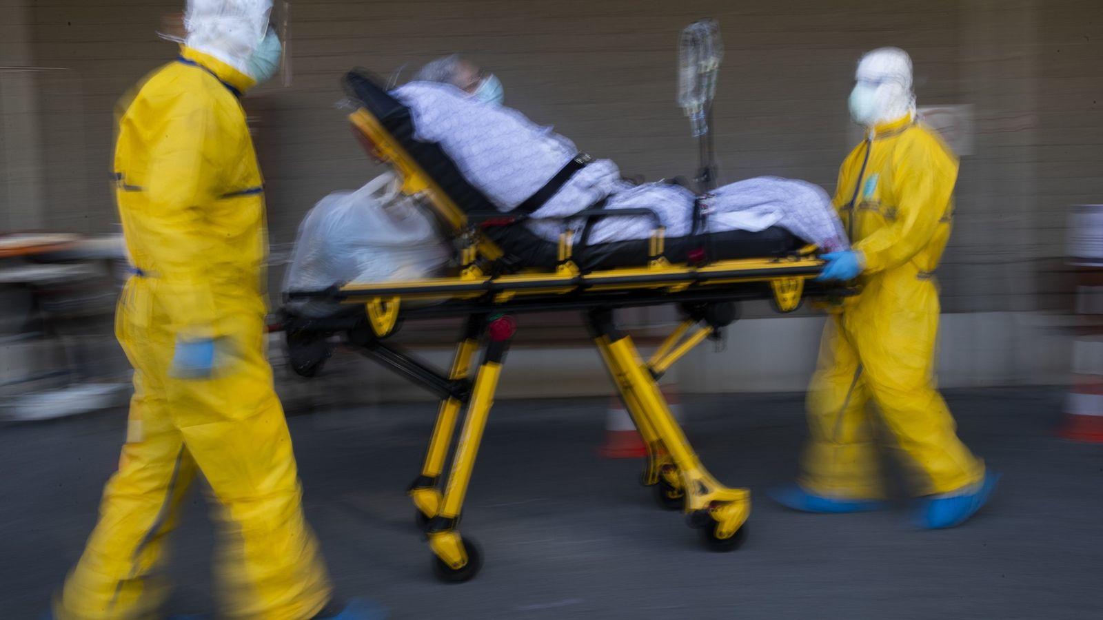 El personal médico de Klinicare, Bruselas, traslada a un paciente con coronavirus de un hospital lleno ...