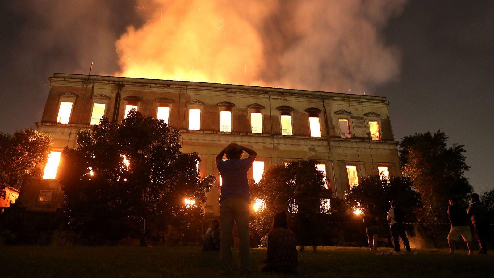 La gente observa mientras el fuego arde en el Museo Nacional de Brasil en Río de ...