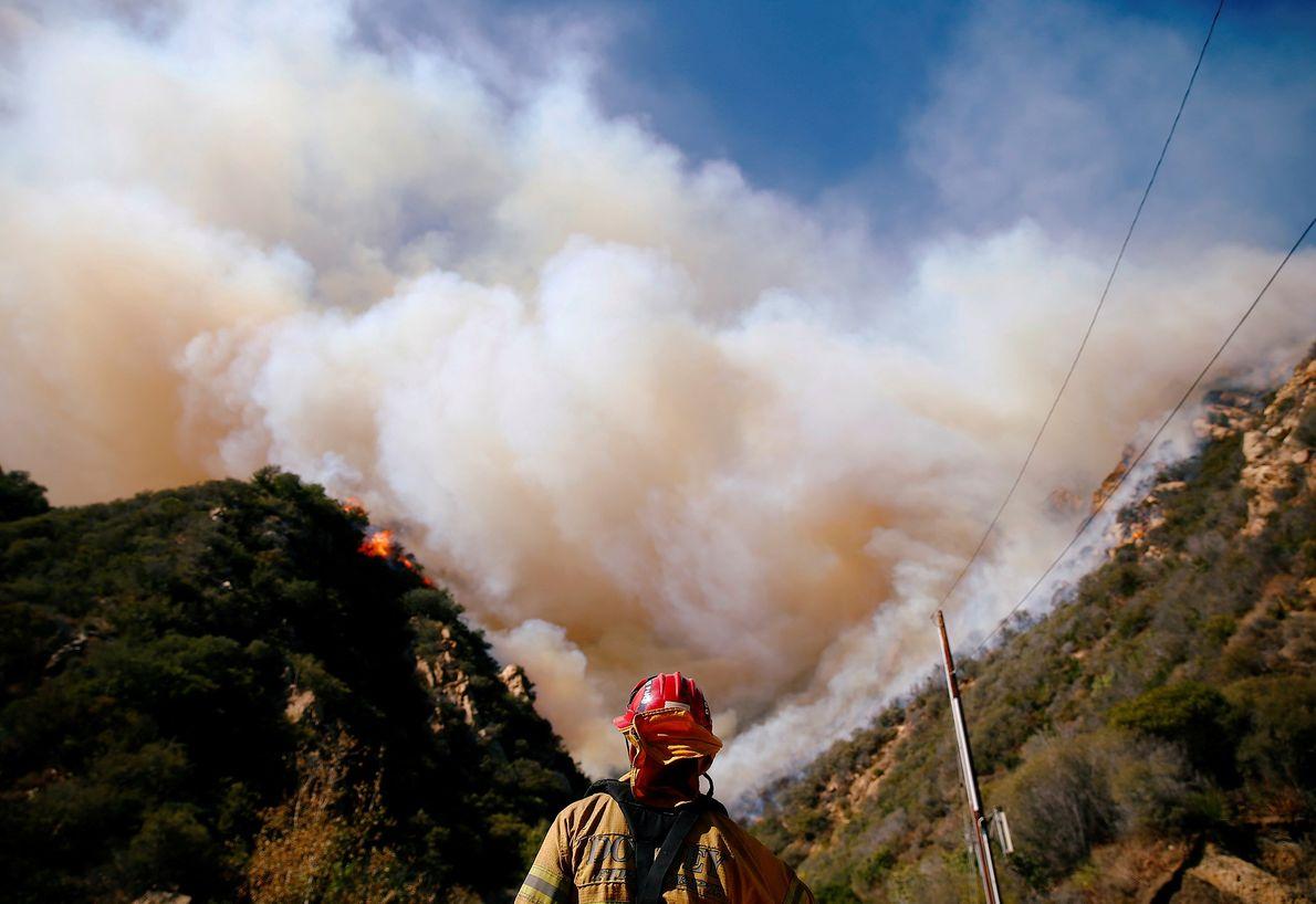 Los bomberos combaten el fuego de Woolsey mientras arde en Malibu, California, el lunes.