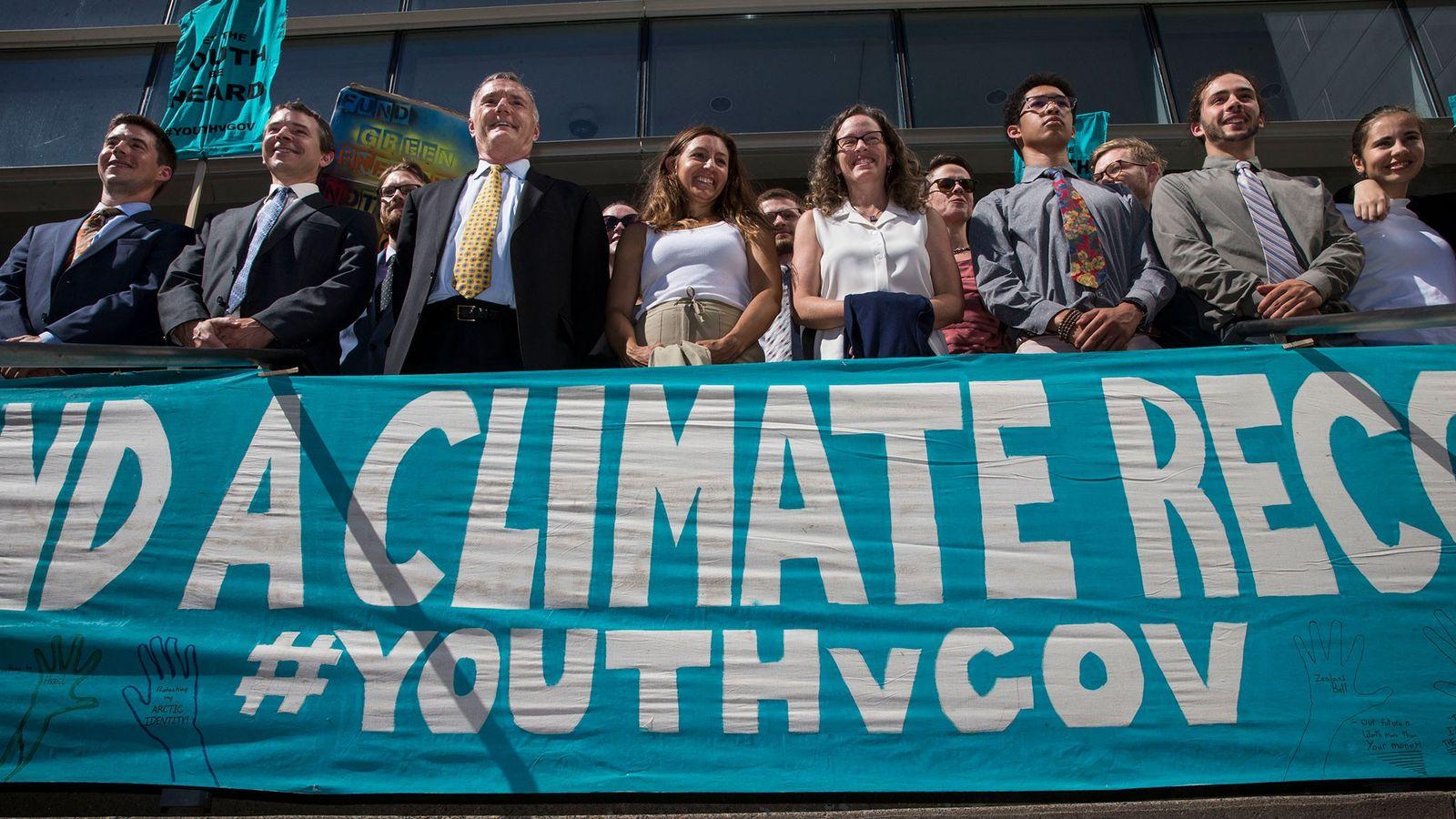 Los abogados y los jóvenes demandantes se alinean detrás de una pancarta después de una audiencia ...
