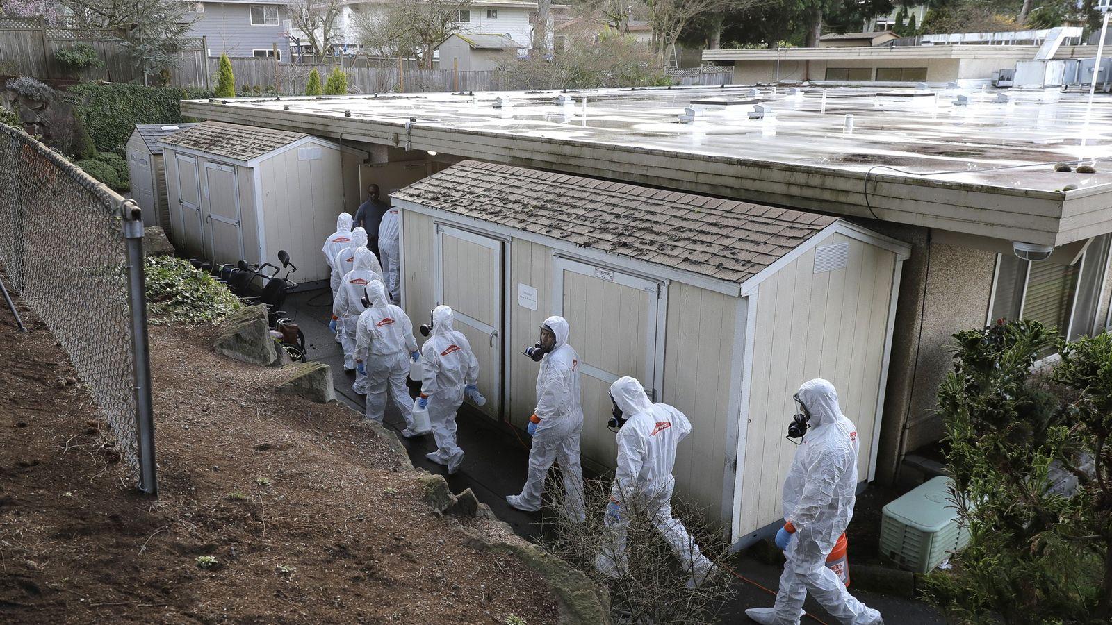 Los trabajadores de un equipo de recuperación de desastres de Servpro usan trajes protectores y respiradores ...