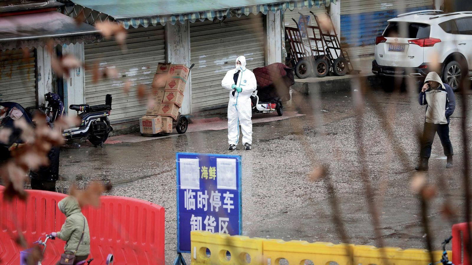 Un trabajador con traje de protección en el mercado de mariscos en Wuhan, China, en el ...