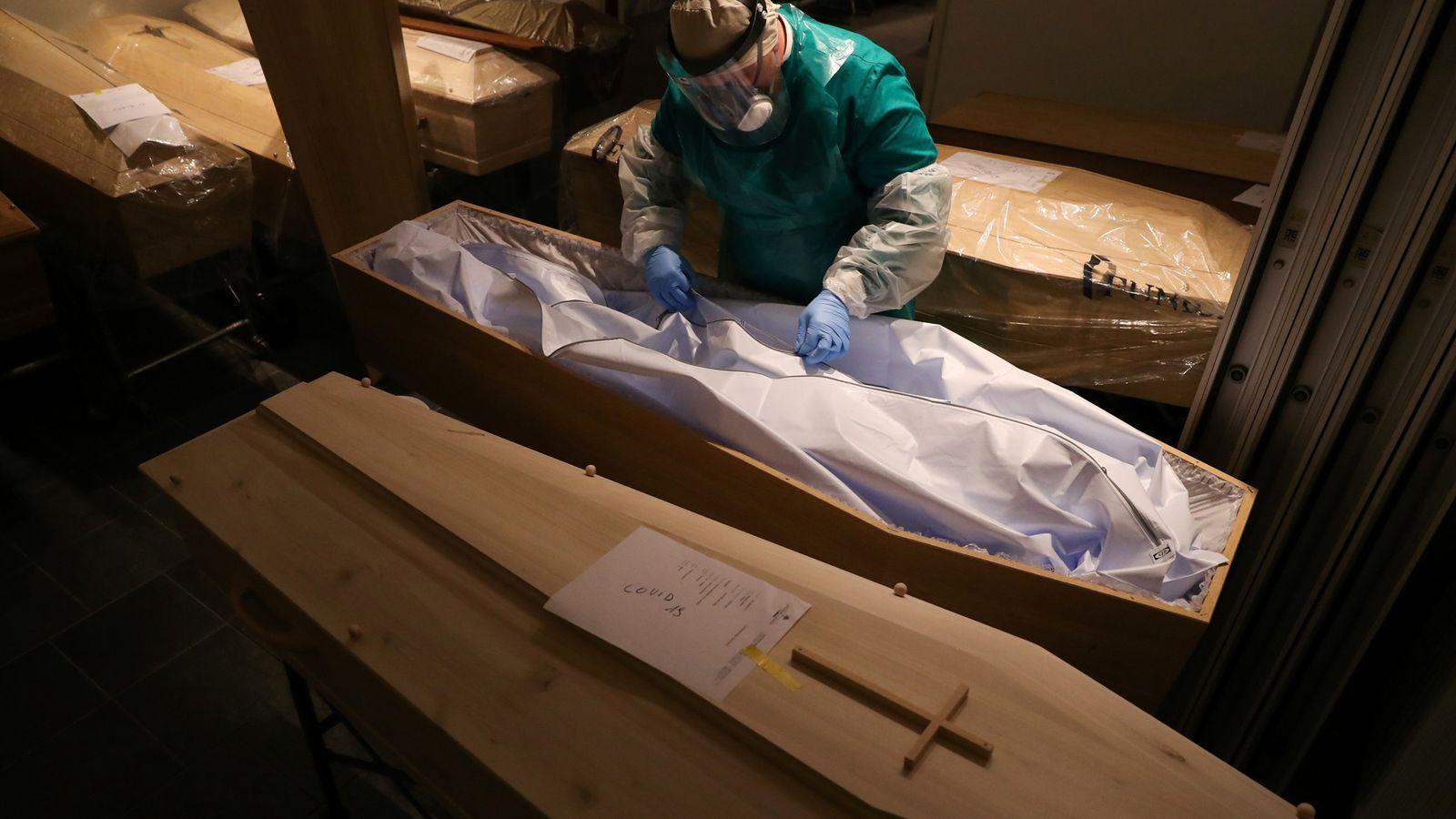 Un empleado de una morgue, con un traje de protección especial, mira dentro de un ataúd ...