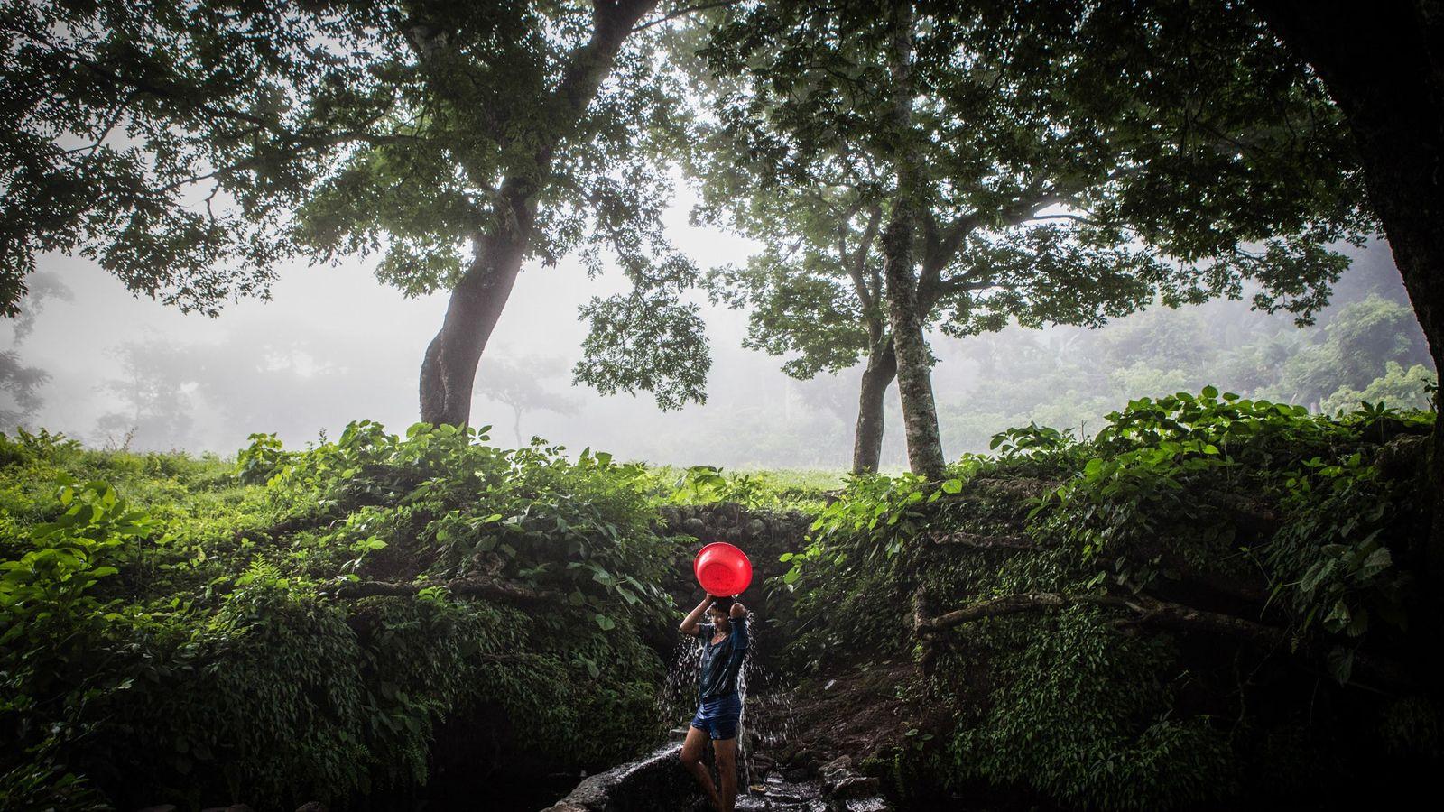 Una niña se lava el cabello en un pozo al amanecer en una pequeña comunidad en ...