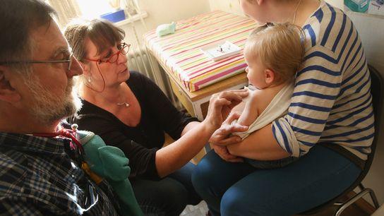 La ayudante de un médico prepara a Tijana, de 11 meses de edad, para una vacuna ...