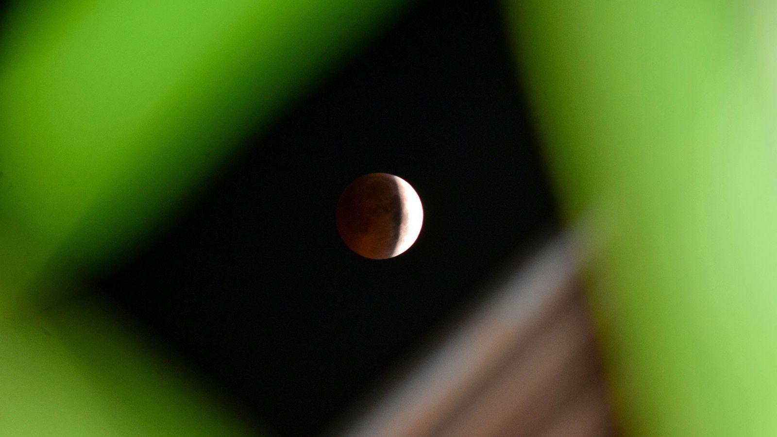 Un eclipse lunar parcial oscurece la cara de la luna vista desde Srinagar, India, en julio ...