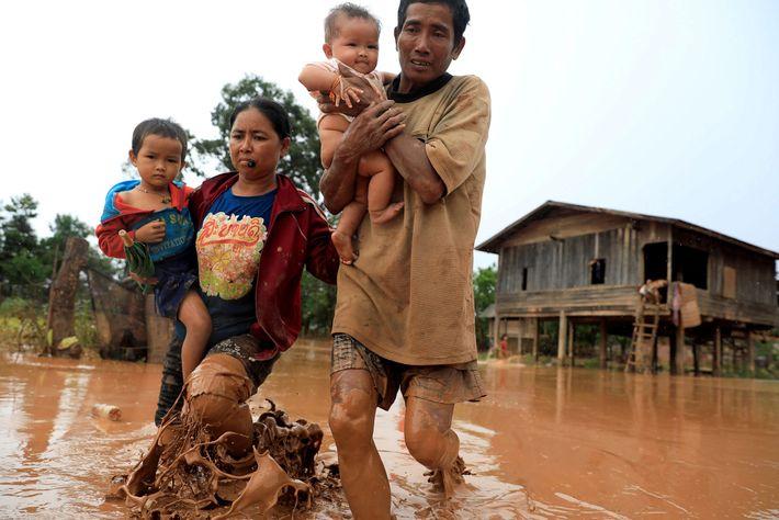 Padres evacuando junto con sus hijos durante una inundación causada por el derrumbe de la represa ...