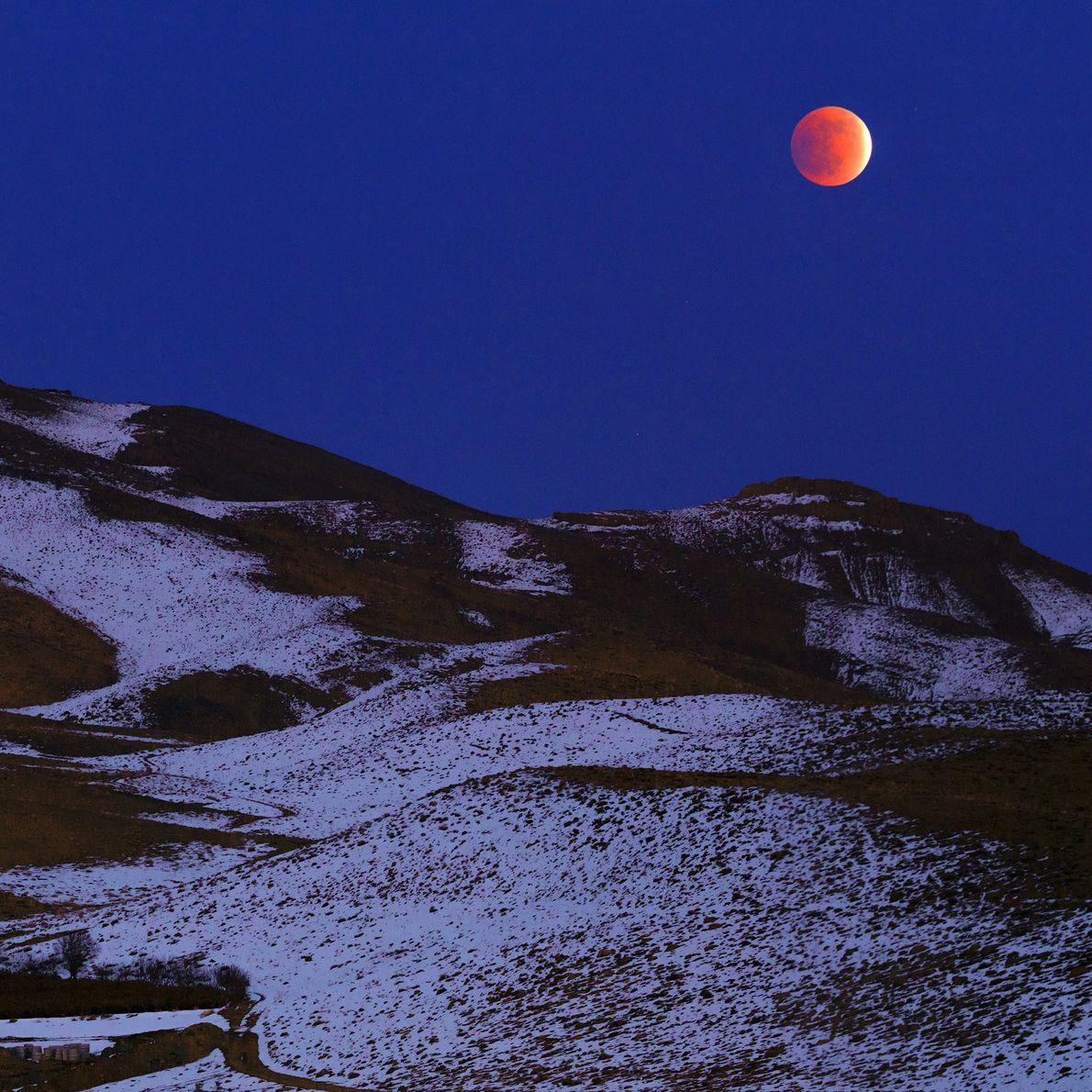 El eclipse lunar total de diciembre del 2011 brilla en el cielo de la tarde sobre ...