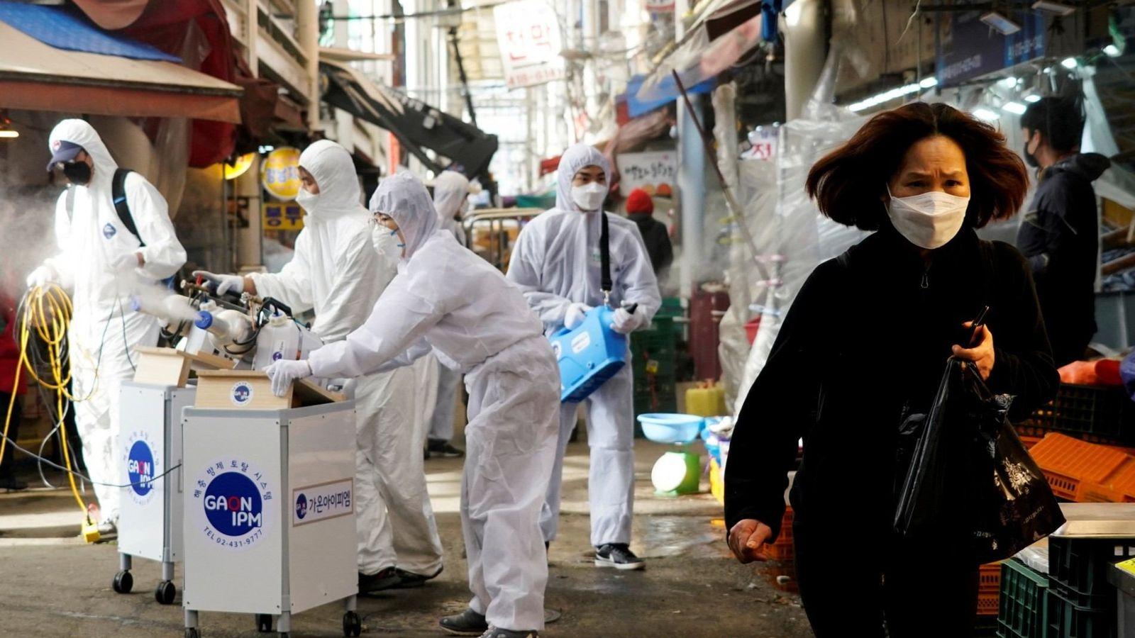 Una mujer que lleva una mascarilla para no contraer el coronavirus reacciona cuando los empleados de ...