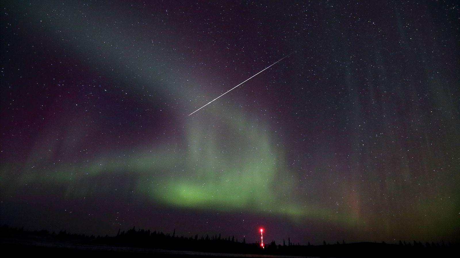 Una estrella fugaz pasa por las auroras del cielo nocturno de noviembre.