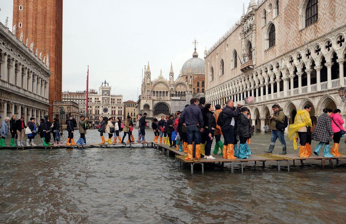 La gente camina sobre una pasarela en la plaza inundada de San Marcos durante el período ...