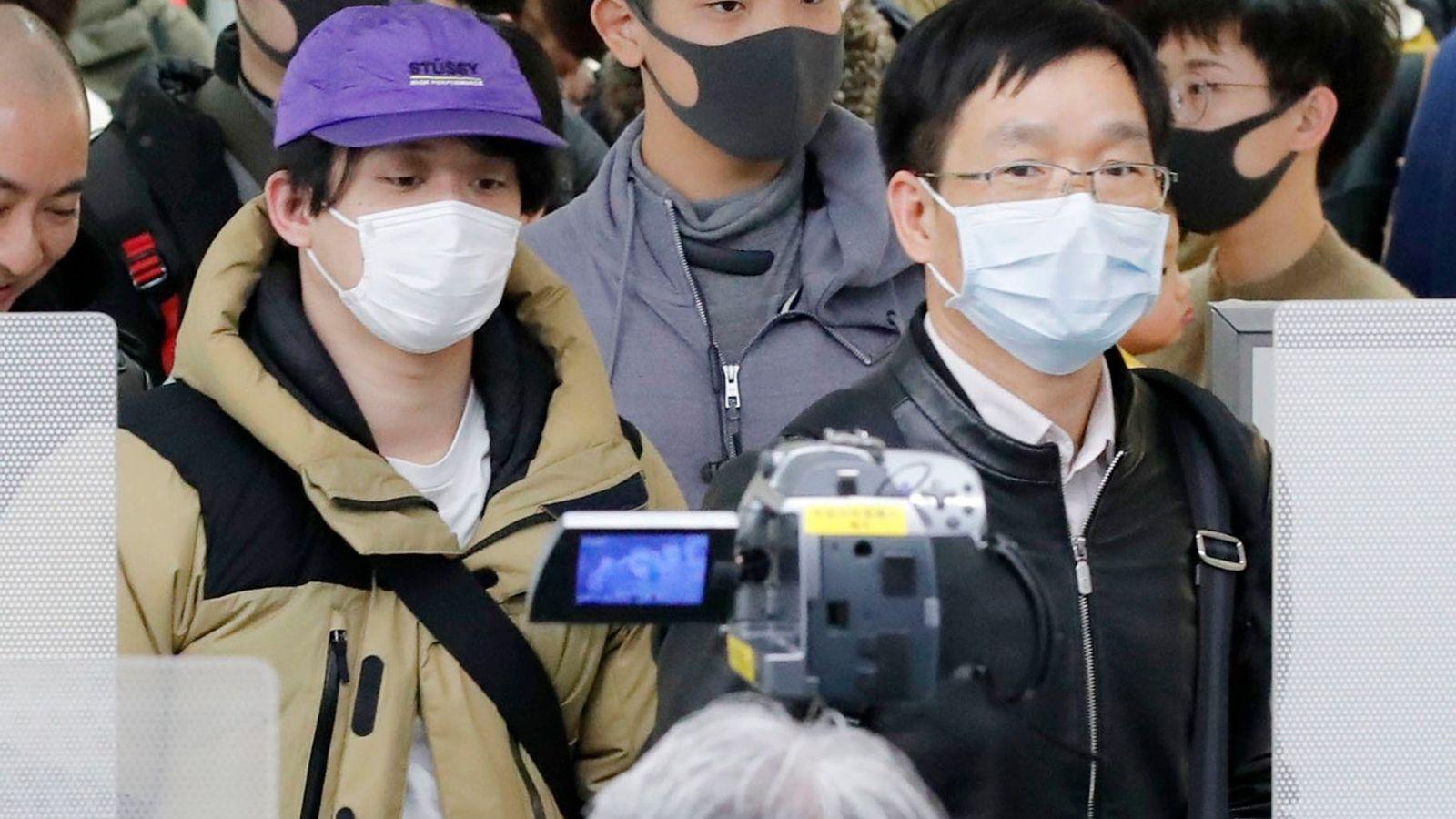 Pasajeros que viajaban desde la ciudad china de Wuhan, epicentro del nuevo coronavirus que provoca neumonía, ...