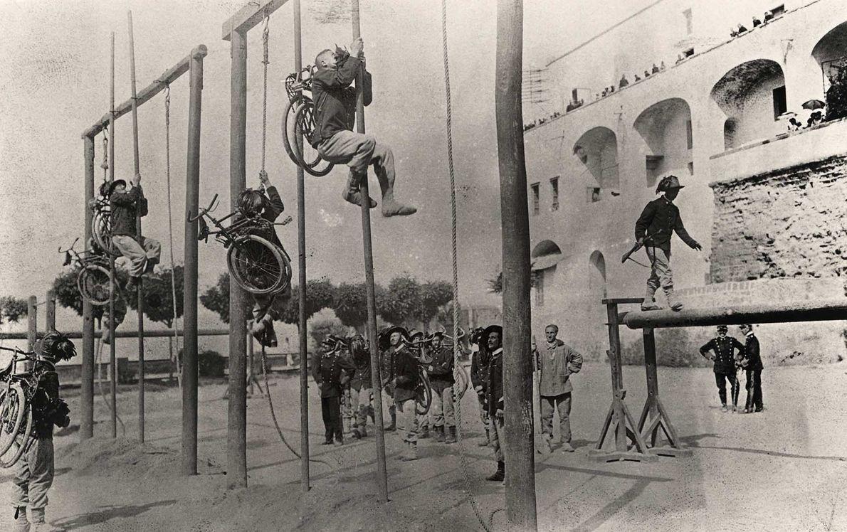Los miembros del cuerpo de caballería ciclista del ejército italiano escalaban con sus bicicletas cargadas a …