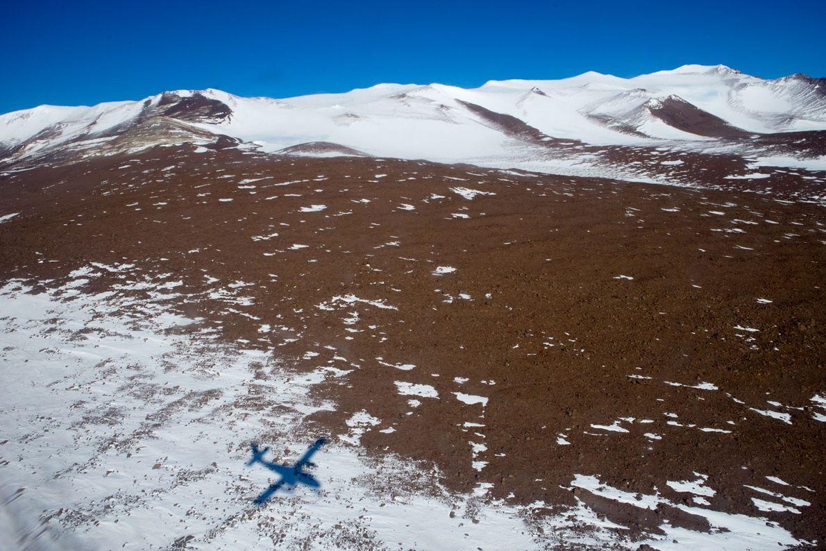 La sombra de una avioneta Twin Otter zumba cerca del suelo sobre Graphite Peak. Debido a ...