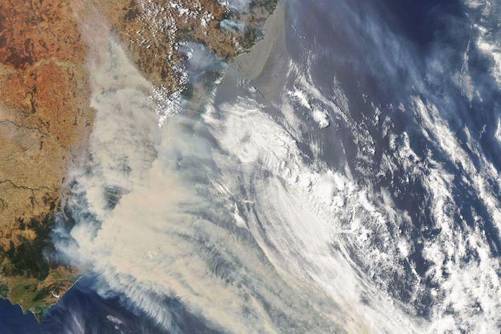 En esta imagen satelital de la NASA se observa humo y nubes que se originan en ...