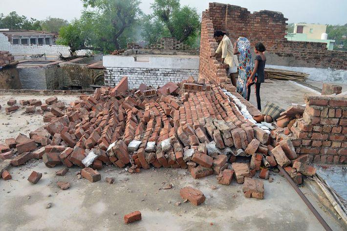 Residentes de la India observan una pared destruida por los fuertes vientos durante una tormenta de ...