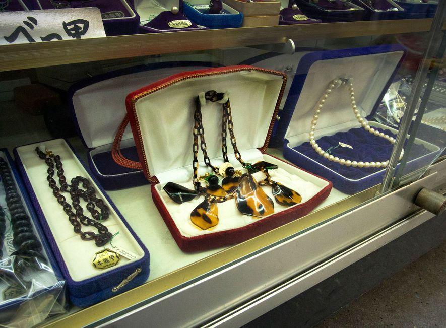 Las tiendas de regalos de las calles de Enoshima, Japón, exhiben artículos como este collar, fabricado ...