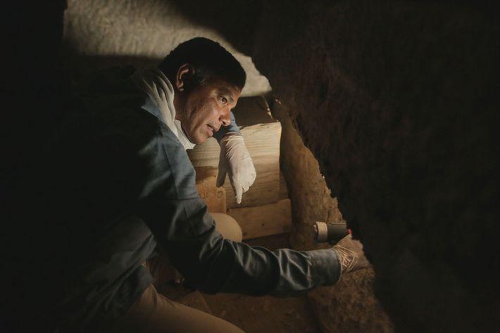 Ramadan Hussein echa un vistazo dentro de un sarcófago de piedra en busca de momias. El ...
