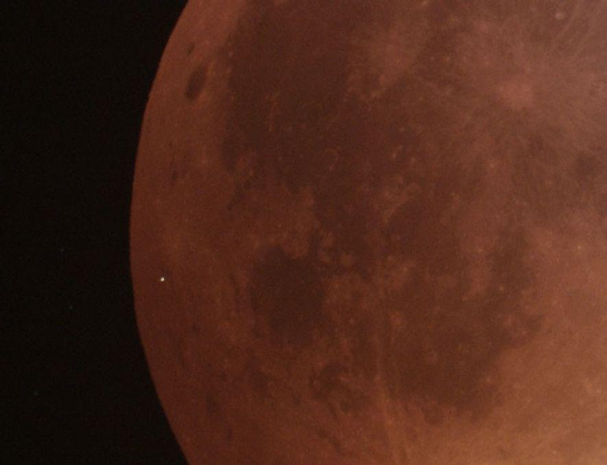 """Un primer plano de la cara oscurecida de la """"luna de sangre"""" muestra el destello del ..."""