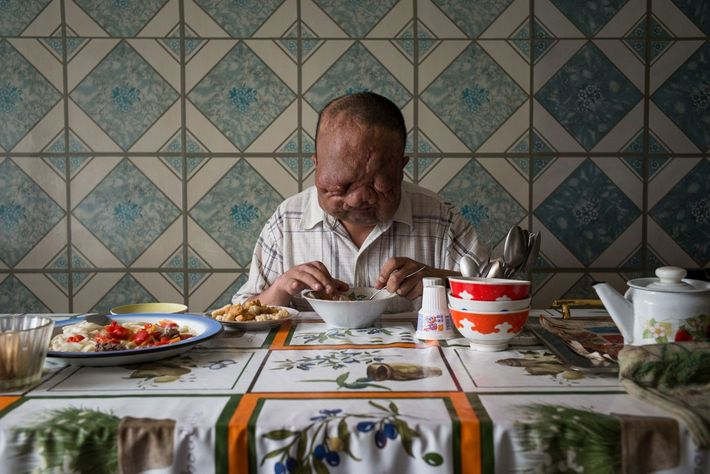 Berik Syzdykov, de 38 años, sentado en la mesa de la cocina en el piso que ...
