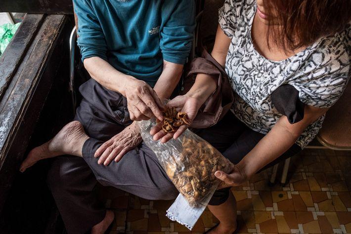 Una mujer vietnamita consulta con un practicante de medicina tradicional sobre el uso de las escamas ...
