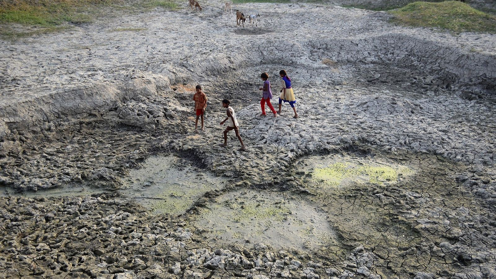 Niños indios juegan en una zona seca del encogido río Varuna, un afluente del río Ganges.
