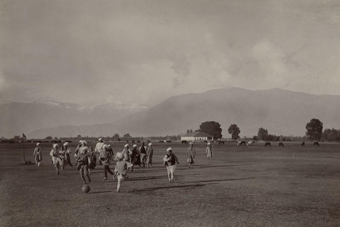 Niños juegan al fútbol callejero En un amplio campo al pie del Himalaya.